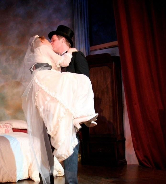 Actor Kevin Curran (Michael) carries Margaret Smith (Agnes) across the threshold in The Montgomery Theatre production of The Fourposter.  The bridal dress is a reproduction of the one worn by L.M. Montgomery for her own wedding in 1910.